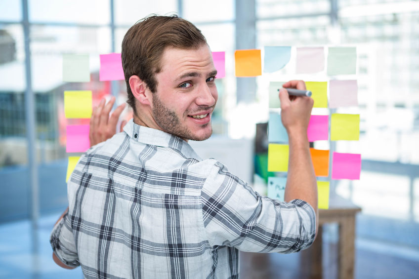 52799522 - hipster man writing on post-it in office